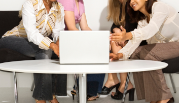 diverse women gather around a laptop
