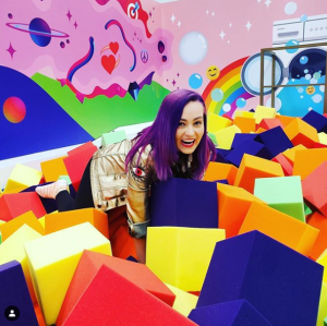 Molly Burke is looking up and laughing at the camera. She is so happy as she is in the middle of colorful foam blocks that are in a very fun foam pit in the Instagram lounge