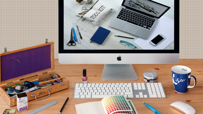 wooden desk with iMac and magic mouse and keyboard has color samples and other design tools scattered about, an image of a toolkit laptop and smartphone is on the screen